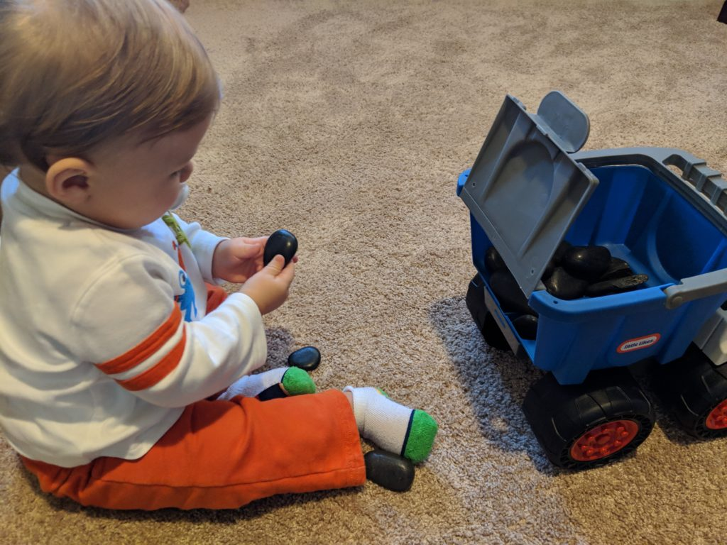 Little man playing with his dump truck and rocks.