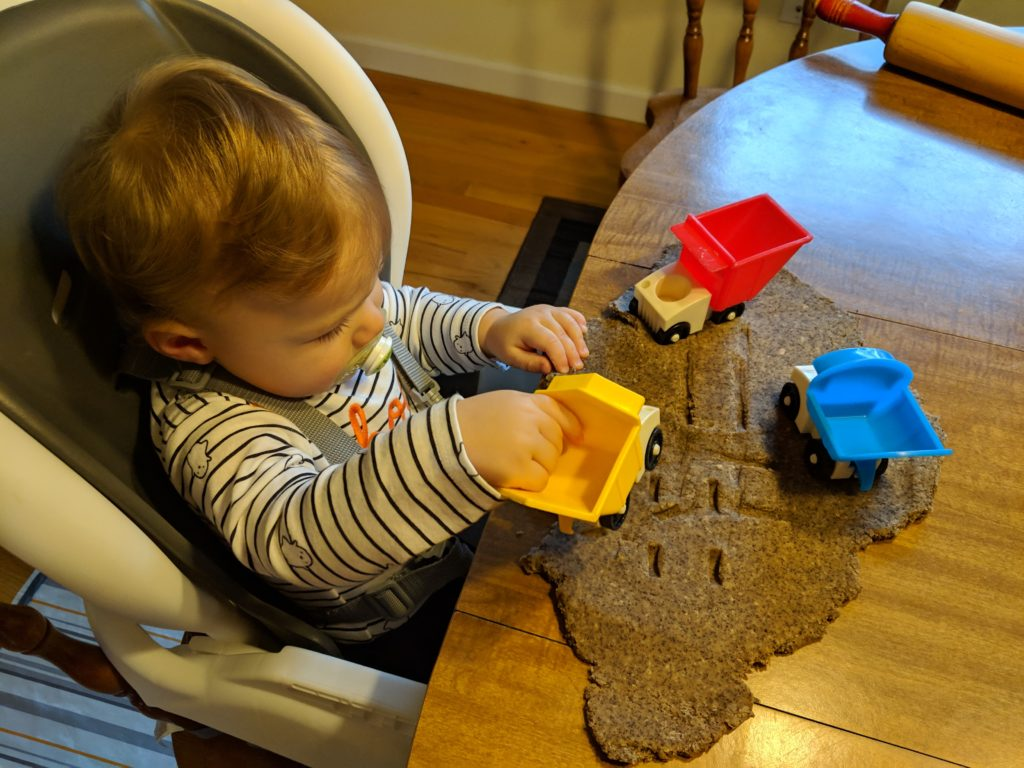 Little man playing with his playdoh and trucks.