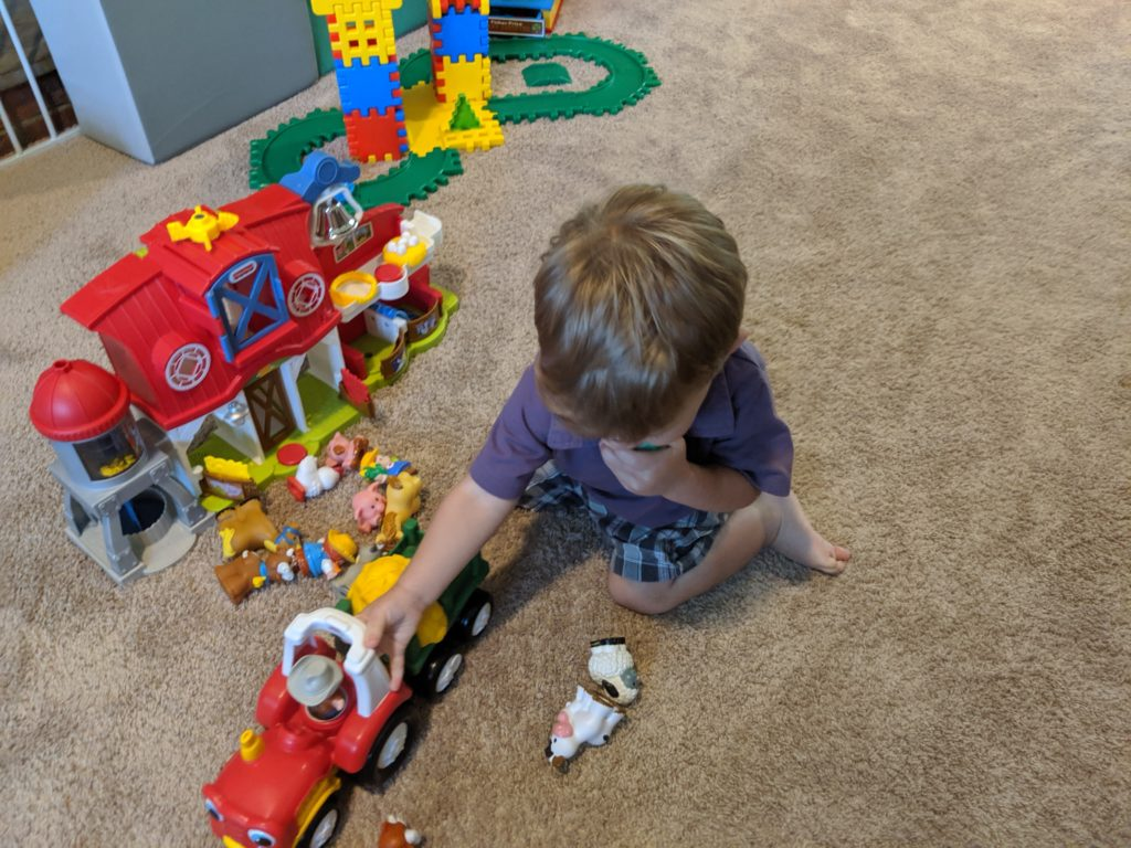 Little Man playing with his Farm set from Fisher Price