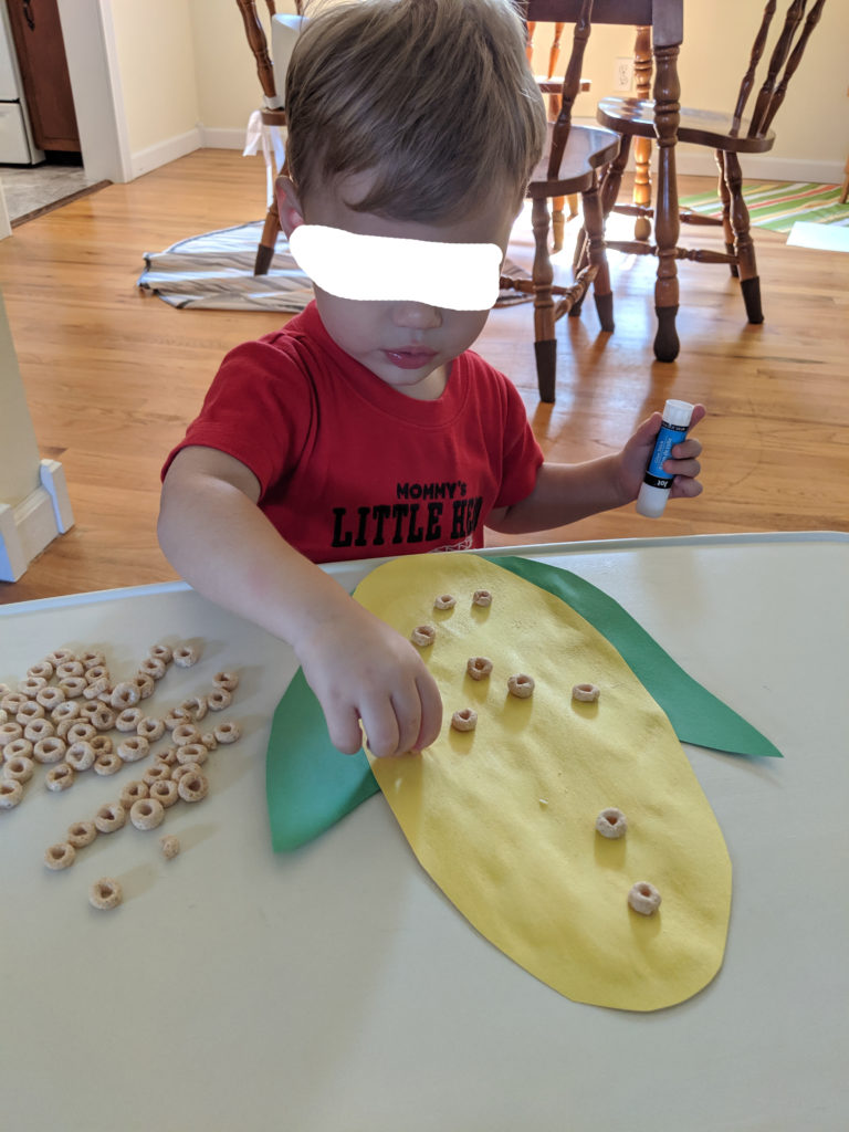 Little Man creating his corn cob.