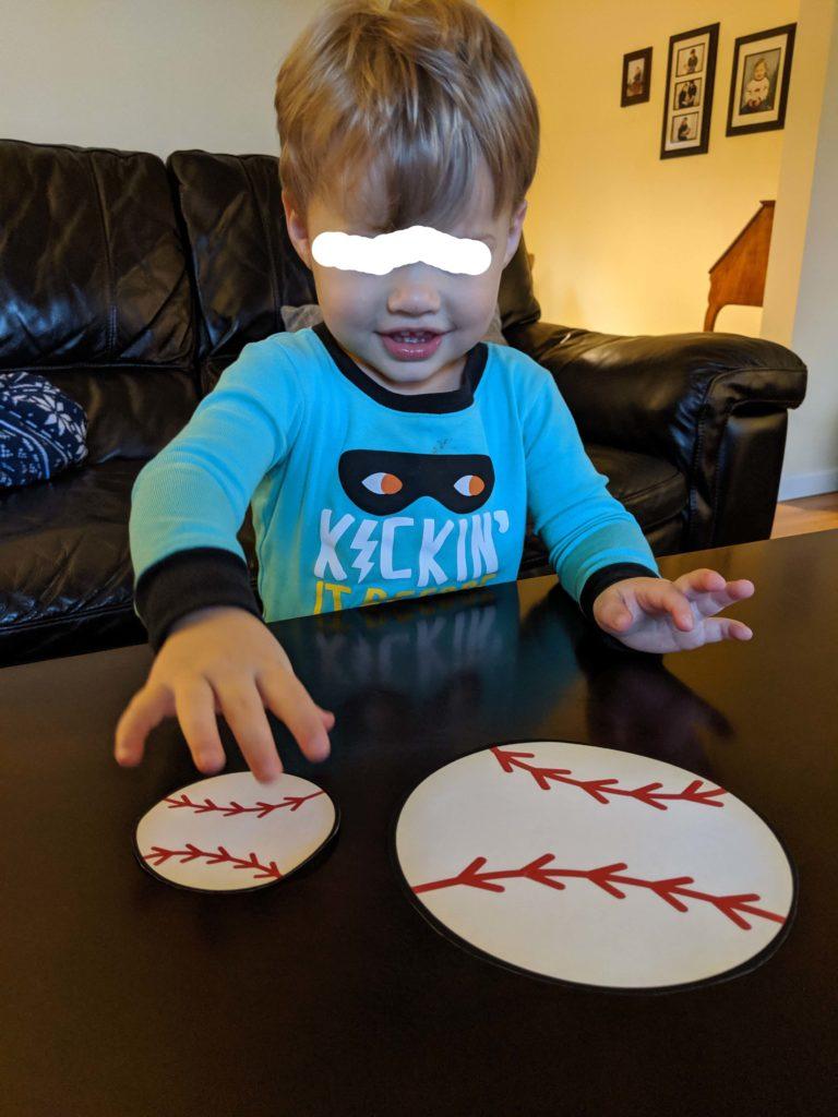Little Man choosing the little baseball.