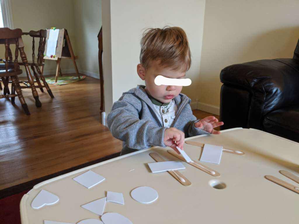 Little Man gluing his shapes!