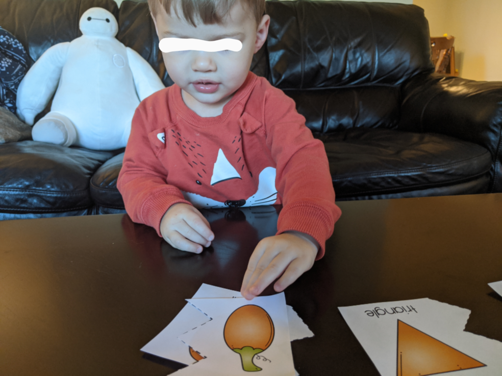 Little Man completing Fall shape puzzle.