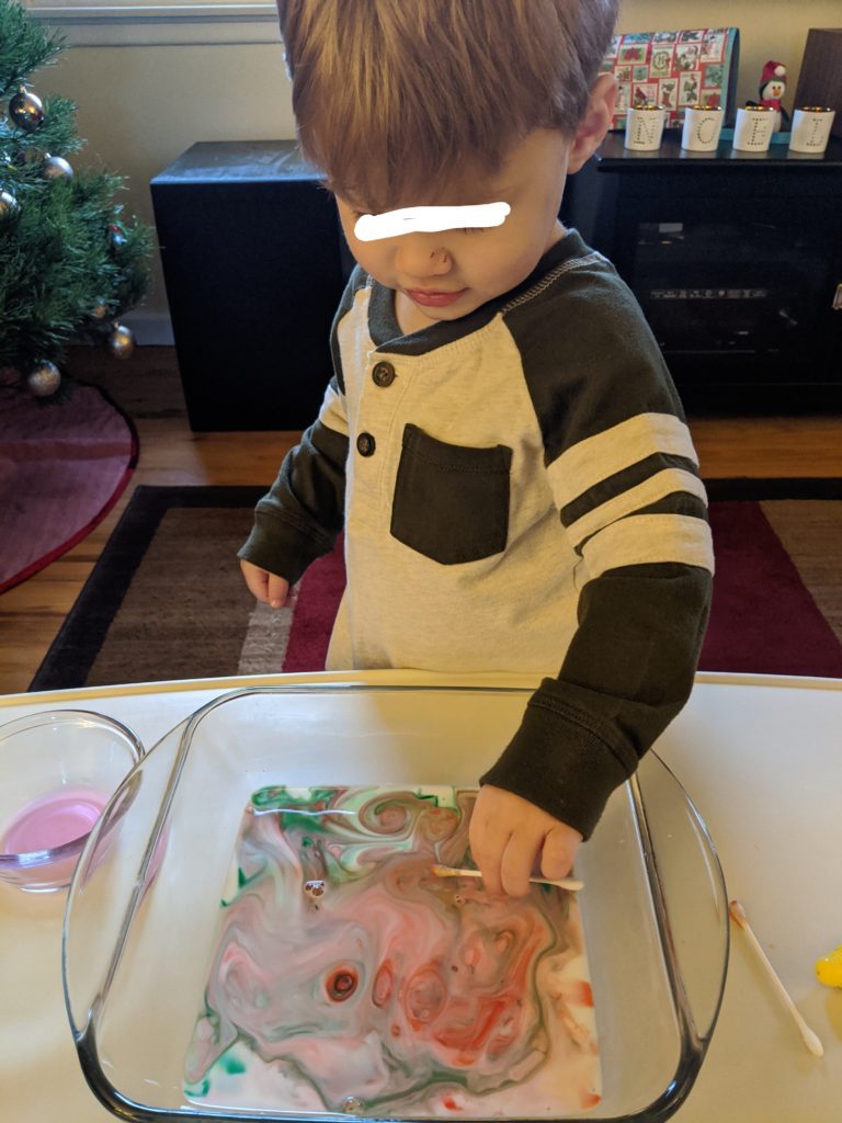 Little Man trying the Magic Milk Christmas Activity.