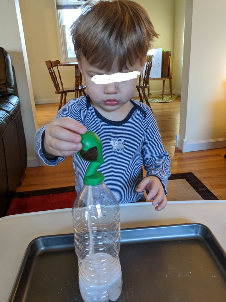 Little Man dumping the baking soda into the vinegar.